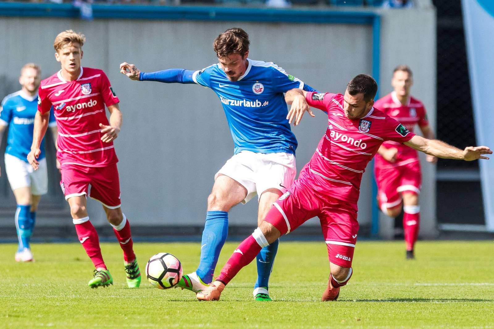Massimo Ornatelli grätscht gegen Dennis Erdmann. Jetzt auf FSV Frankfurt gegen Hansa Rostock wetten!