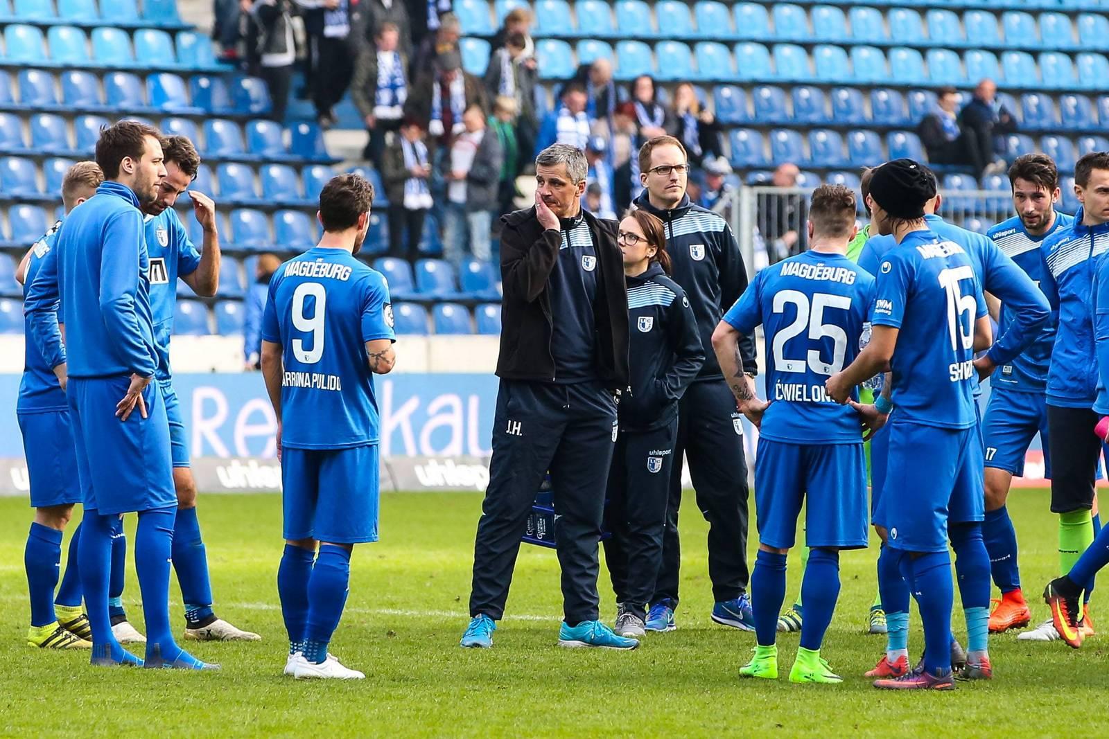 Magdeburgs Trainer Jens Härtel wird umringt von seinen Spielern.