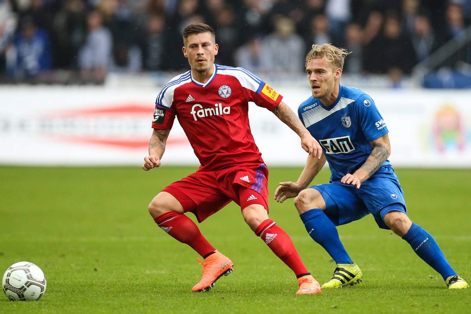 Zweikampf zwischen Steven Lewerenz und Nils Butzen. Jetzt auf Holstein Kiel gegen Magdeburg wetten!