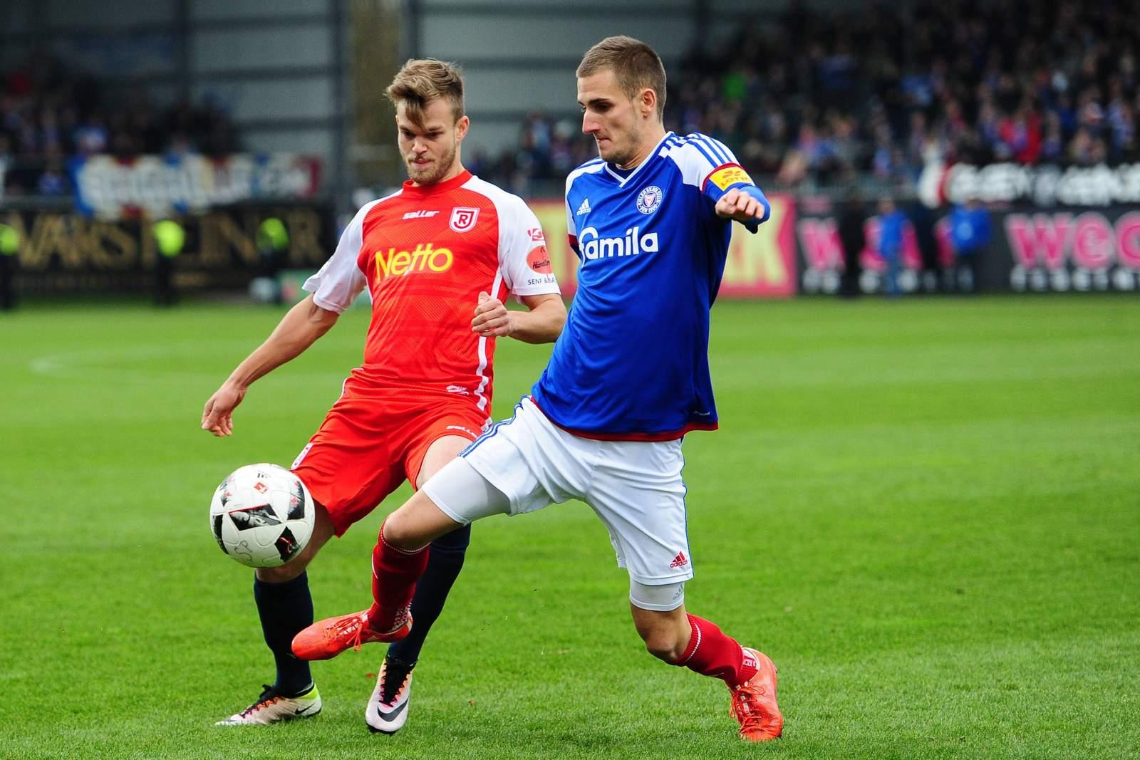 Dominick Drexler und Benedikt Saller im Duell um den Ball. Jetzt auf Regensburg gegen Kiel wetten!