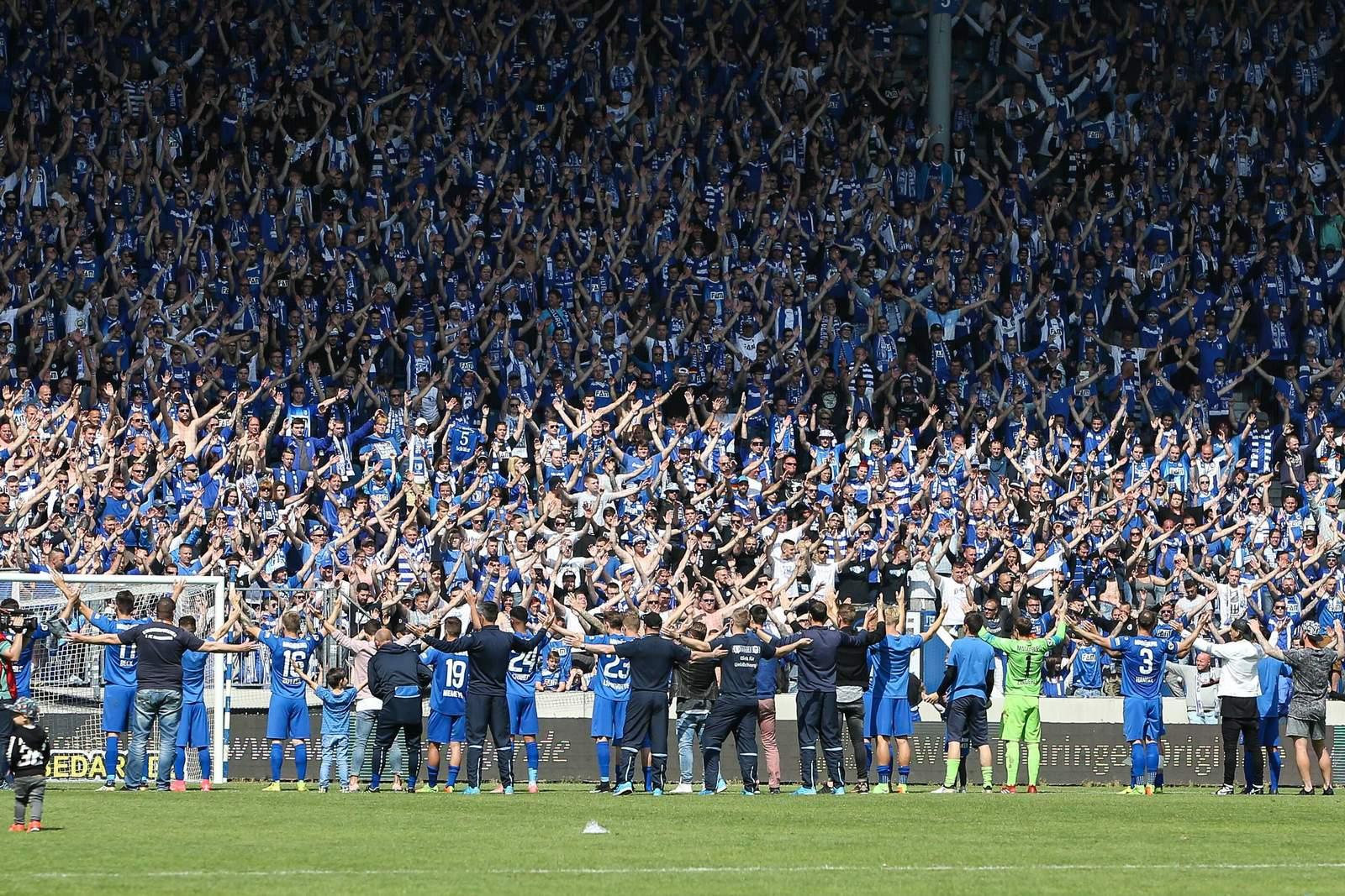 Fans vom 1.FC Magdeburg feiern mit der Mannschaft