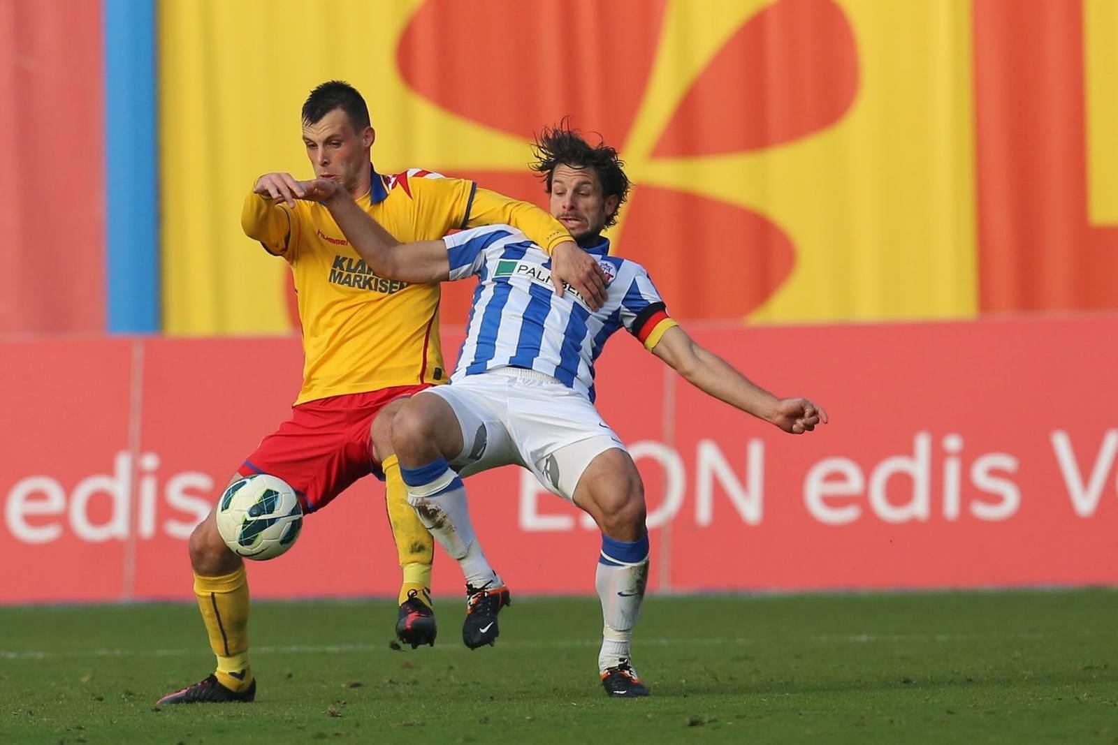 Koen van der Biezen und Sebastian Pelzer im Duell. Jetzt auf die Partie Rostock gegen Karlsruhe wetten