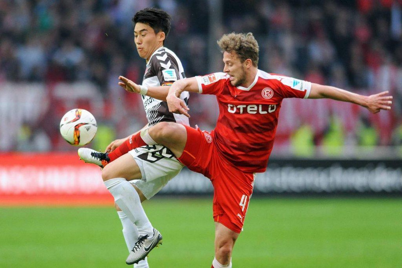 Kyoung-Rok Choi im Trikot des FC St. Pauli gegen Julian Schauerte von Fortuna Düsseldorf