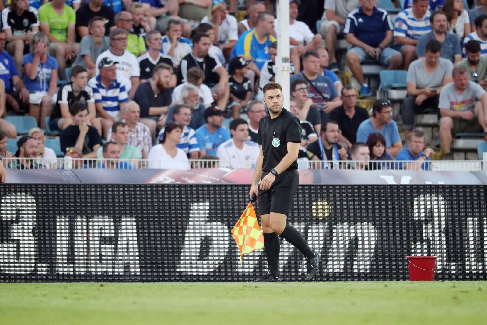 Schiedsrichter-Assistent vor bwin Bandenwerbung in der 3.Liga