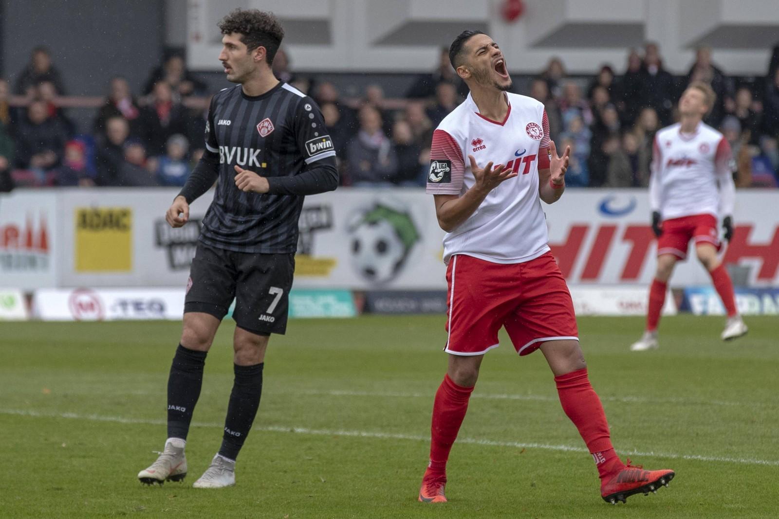 Hamdi Dahmani ärgert sich, Fabio Kaufmann von den Kickers schaut dem Ball nach
