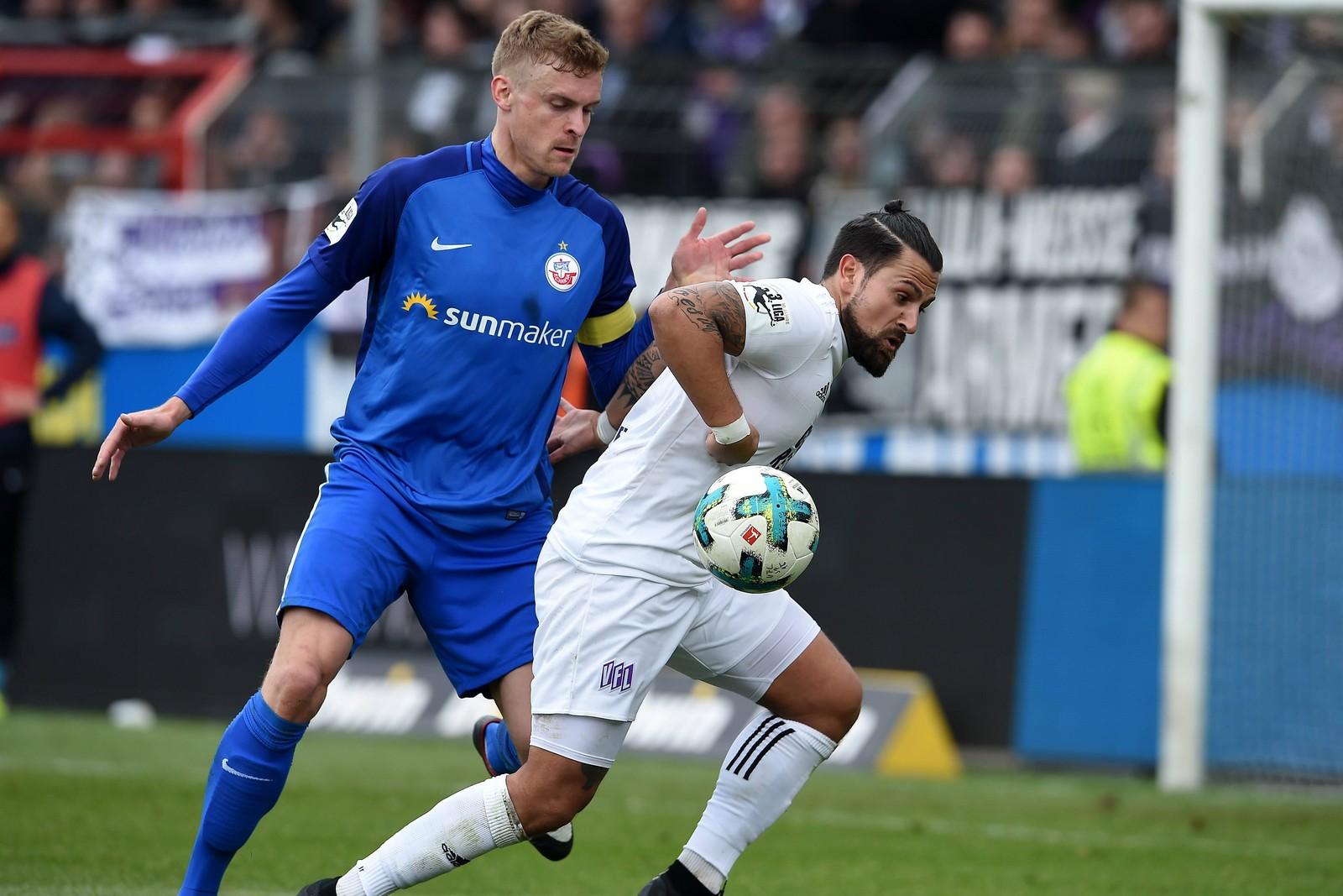 Osnabrücks Marcos Álvarez (r.) schirmt den Ball vor Hansa-Kapitän Oliver Hüsing ab.